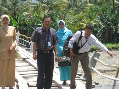 Tim BPS/Pendampingan II Paket Pembelajaran Sains berjalan di atas jembatan yang nyaris ambruk