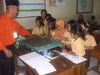 H.Basiran sedang mendemonstrasikan cara menanam padi kepada anak didiknya.