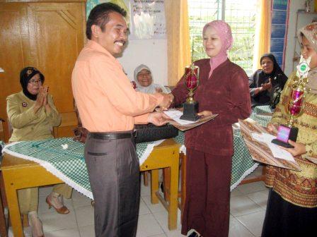 Kadis Pendidikan Sibolga Drs Rustam Manalu memberikan piala kepada Ibu Sri Wahyuni Sitompul sebagai juara I lomba APM.